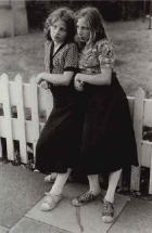Two girls leaning on a fence by Mark Cohen